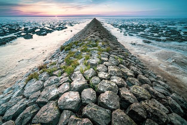 Bela foto de uma praia rochosa durante o pôr do sol