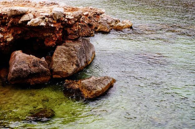 Bela foto de uma praia rochosa durante o tempo ensolarado