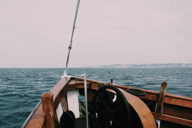 Bela foto de uma proa do barco no mar com colinas e um nublado no fundo