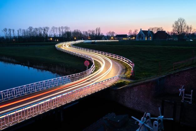 Bela foto de uma rua com trilhas leves de carros ao lado do rio à noite