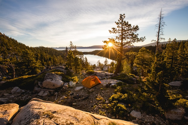 Bela foto de uma tenda laranja na montanha rochosa, rodeada por árvores durante o pôr do sol