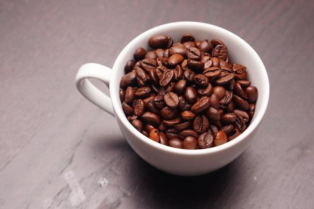 Bela foto de xícara branca cheia de grãos de café em uma mesa de madeira