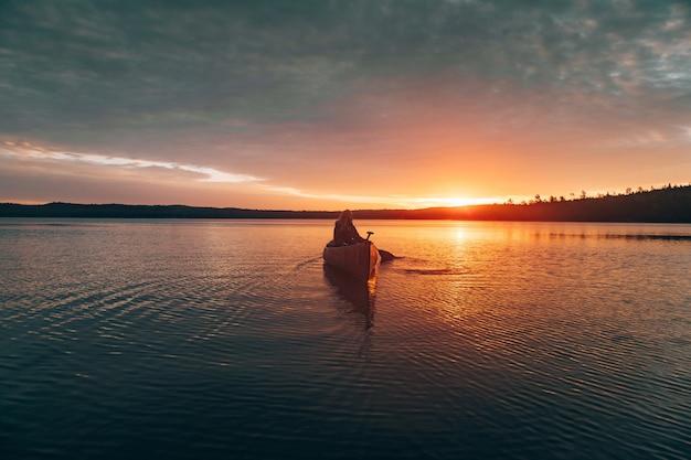 Bela foto distante de uma mulher andando de caiaque no meio de um lago durante o pôr do sol