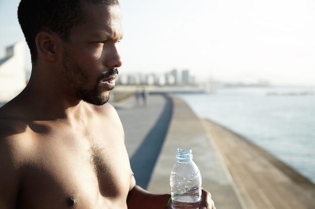 Bela foto do afro-americano seminu que está cansado pelo calor do verão na cidade grande. jovem, adiar a roupa e segurando uma garrafa de água