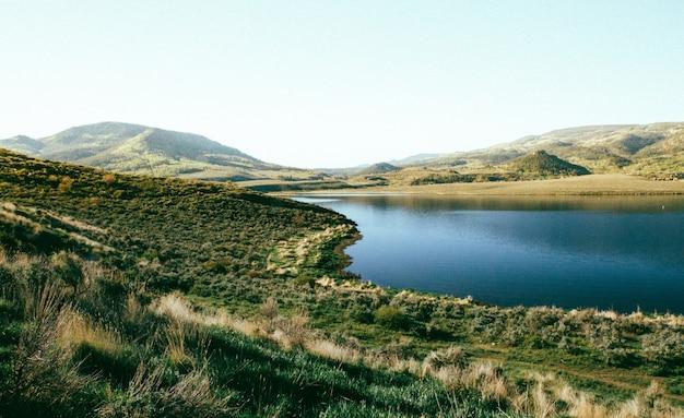 Bela foto do campo gramado perto da água com uma montanha arborizada à distância