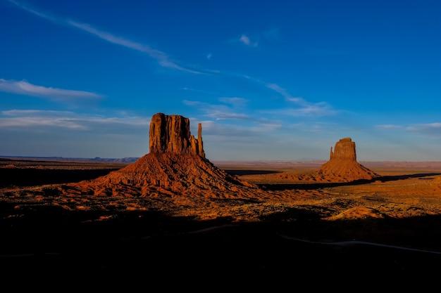 Bela foto do deserto com arbustos secos e grandes falésias à distância sob um céu azul