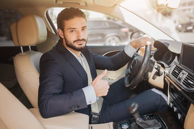 Bela foto do jovem empresário, sentado no carro de luxo e segurando o polegar grande. ele segura uma mão no volante. jovem recomenda este carro.