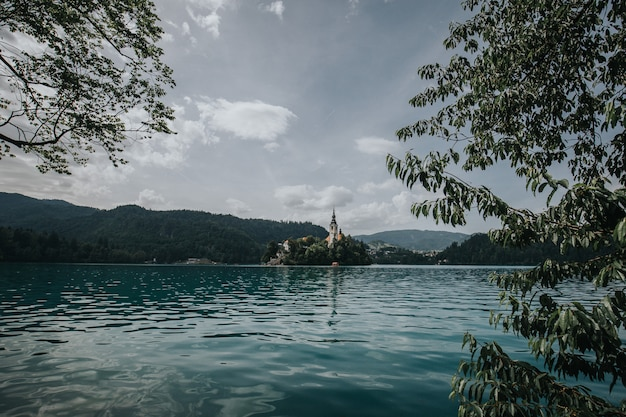Bela foto do lago sangrou com um edifício cercado por árvores ao longe