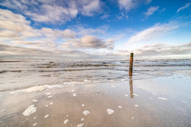 Bela foto do mar chegando à costa sob um céu azul nublado