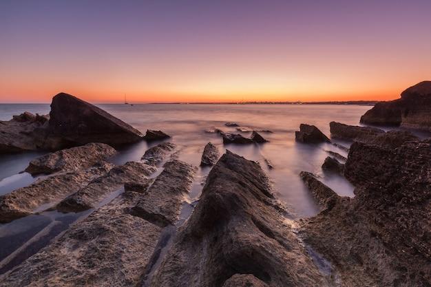 Bela foto do mar com falésias e pedras durante o pôr do sol