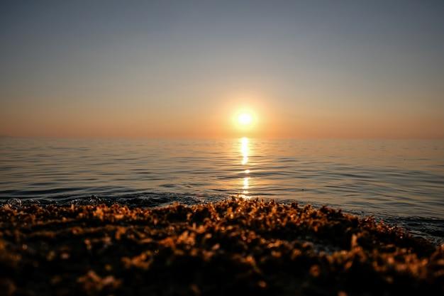 Bela foto do mar com ondas e sol à distância, com céu claro ao pôr do sol