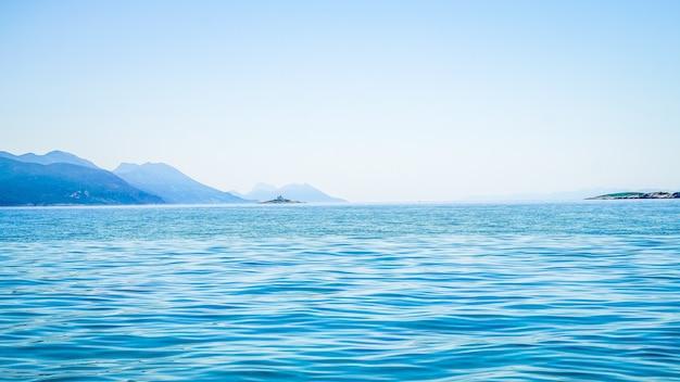 Bela foto do mar com uma montanha à distância e um céu claro