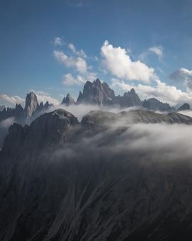 Bela foto do parque natural three peaks parcialmente coberto de nuvens em toblach, itália