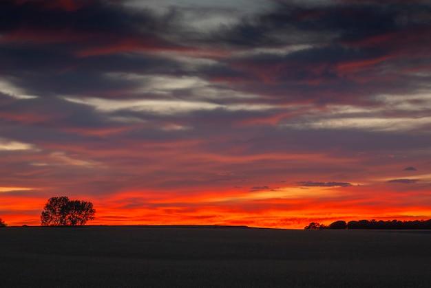 Bela foto do pôr do sol no campo com céu nublado