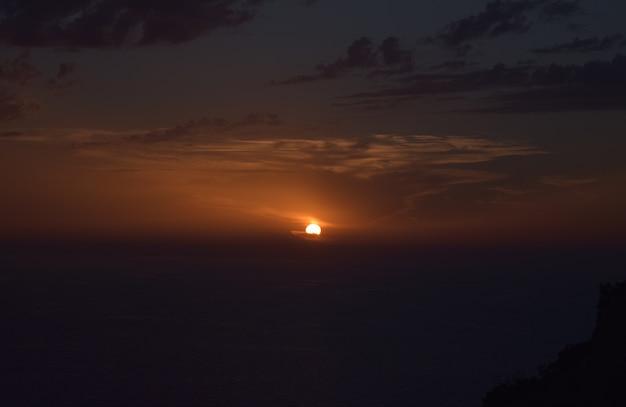 Bela foto do pôr do sol nublado sobre as falésias e o mar em malta