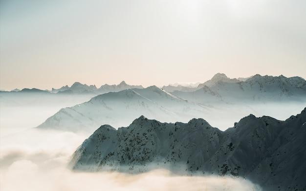 Bela foto do topo das montanhas nevadas acima das nuvens, com um céu claro
