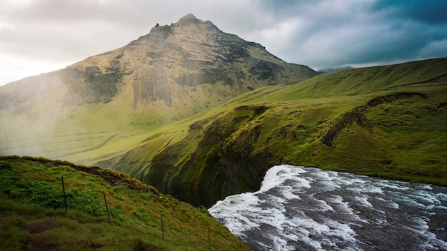 Bela foto do topo de uma cachoeira em montanhas verdes