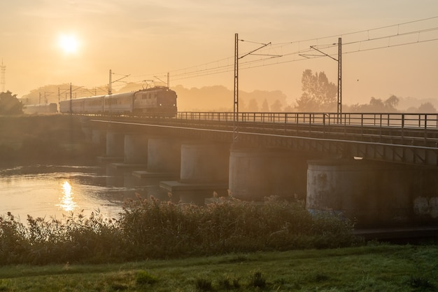 Bela foto do trem passando por uma ponte em um dia ensolarado