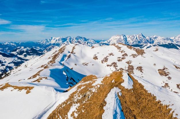 Bela foto dos alpes cobertos de neve com uma cruz em um dos picos sob um céu azul