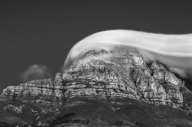 Bela foto em escala de cinza de um penhasco rochoso coberto por nuvens de tirar o fôlego