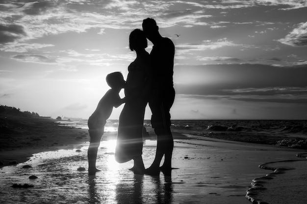 Bela foto em preto e branco de uma família em pé na costa durante o pôr do sol
