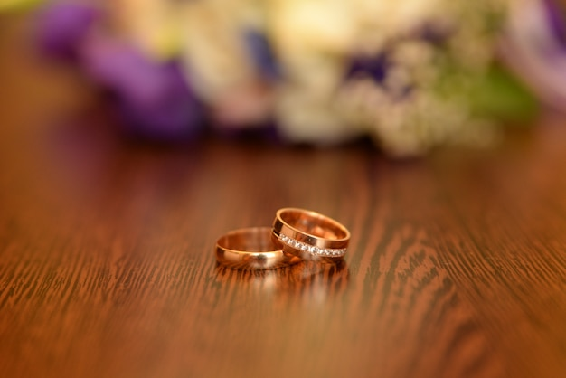 Bela foto enfraquecida com anéis de casamento de mentira sobre uma superfície de madeira