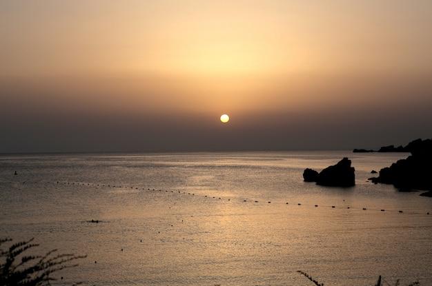 Bela foto grande de um oceano durante o amanhecer com céu rosa