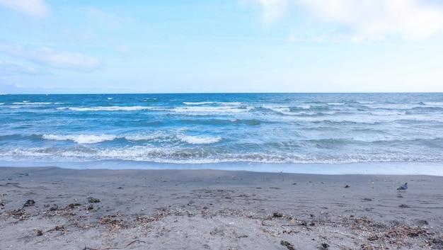 Bela foto grande de uma praia arenosa com incríveis ondas do mar e céu azul
