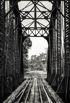 Bela foto preto e branca de uma ferrovia em uma ponte de metal