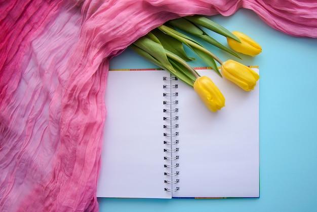 Bela foto romântica com bloco de notas, chá e tulipas em fundo azul