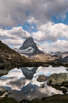 Bela foto vertical de um lago cercado por montanhas, com um reflexo de uma pessoa na água