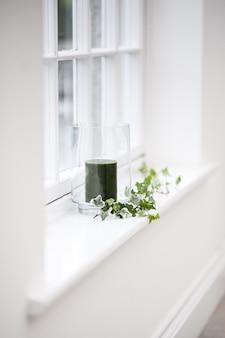 Bela foto vertical de uma vela preta em um copo decorado com folhas em uma prateleira da janela