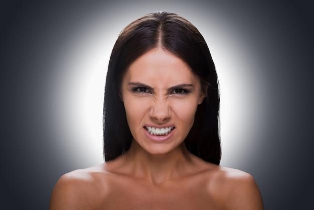 Bela furiosa. retrato de uma jovem furiosa sem camisa, olhando para a câmera e fazendo uma careta em pé contra um fundo cinza