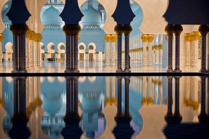 Bela galeria da famosa mesquita sheikh zayed white em abu dhabi, emirados árabes unidos à noite