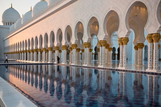 Bela galeria da famosa mesquita sheikh zayed white em abu dhabi, emirados árabes unidos. reflexos ao pôr do sol