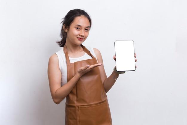 Bela garçonete asiática demonstrando telefone celular em fundo branco