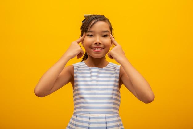 Bela garota asiática, sentado no fundo amarelo