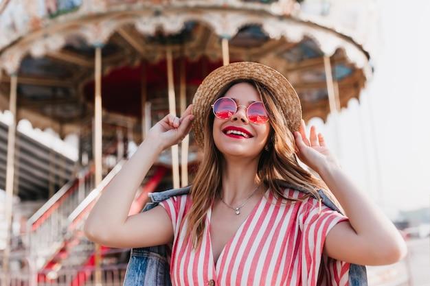 Bela garota de cabelos louros tocando seu chapéu de palha e rindo num dia de verão. foto ao ar livre de alegre mulher europeia posando em frente ao carrossel.