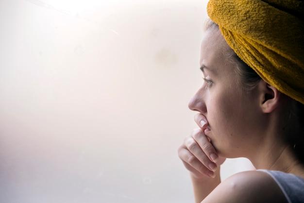 Bela garota de pé na janela assistindo. linda menina triste e solitária sentada perto da janela está perdendo