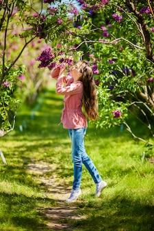 Bela garota desfrutando de jardim lilás