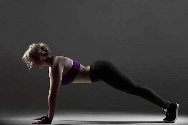 Bela garota desportiva fazendo flexões