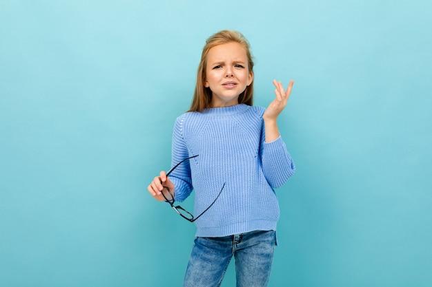 Bela garota europeia é vesgo com óculos na mão na parede azul claro