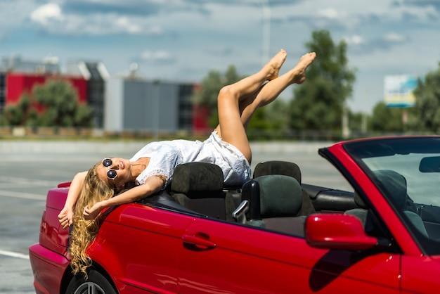 Bela garota loira em um carro vermelho conversível. dia ensolarado