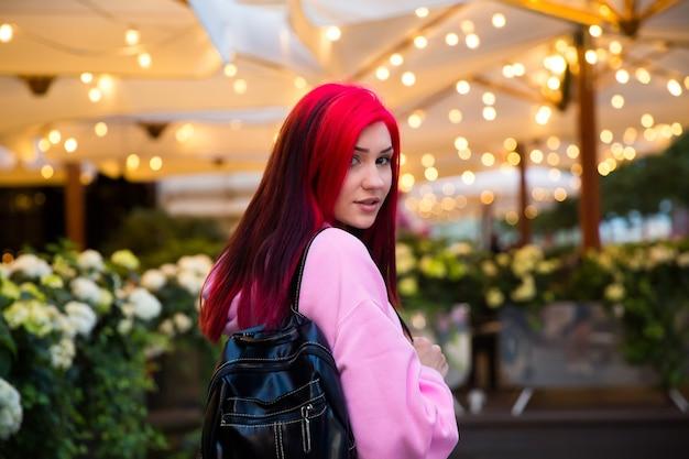 Bela garota ruiva à noite em uma rua iluminada da cidade.