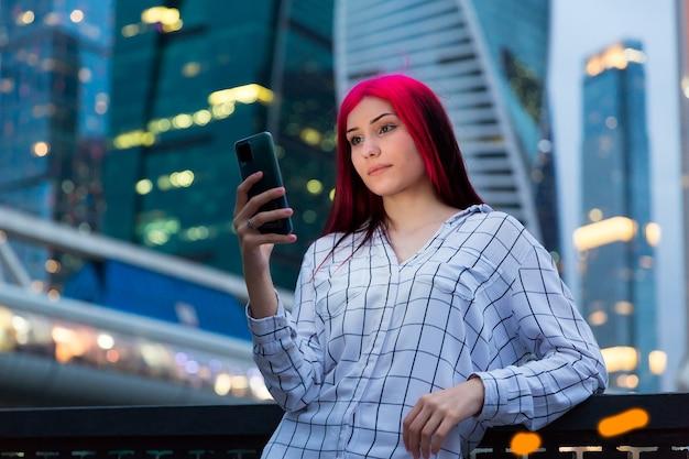 Bela garota ruiva com smartphone à noite na rua iluminada da cidade.