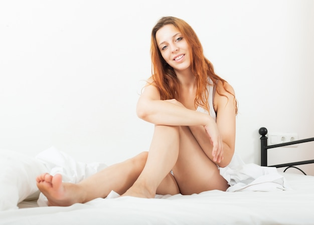 Bela garota sensual de cabelos vermelhos na camisa, acordando na folha branca na cama