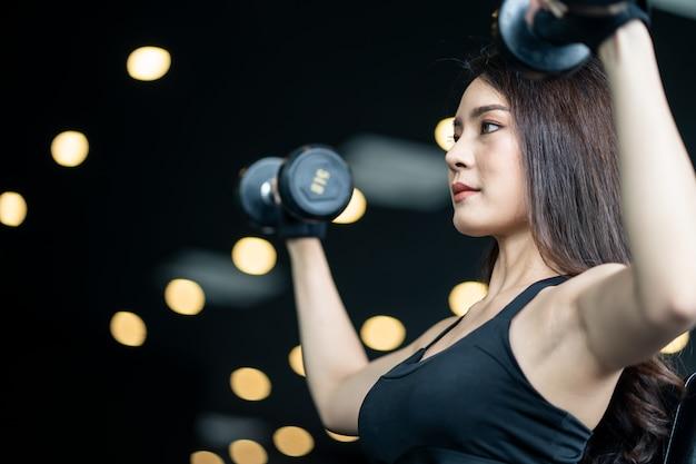 Bela garota sexy asiática no sportswear, levantando os halteres em ambas as mãos.