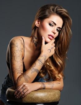 Bela garota sexy com uma tatuagem no corpo. retrato de uma jovem mulher atraente adulta com cabelo castanho.