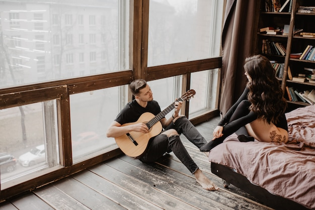 Bela garota sexy e seu namorado tocando violão
