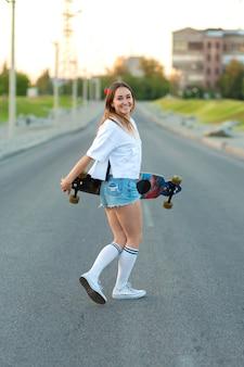 Bela garota sexy em shorts curtos, andando com longboard em tempo ensolarado